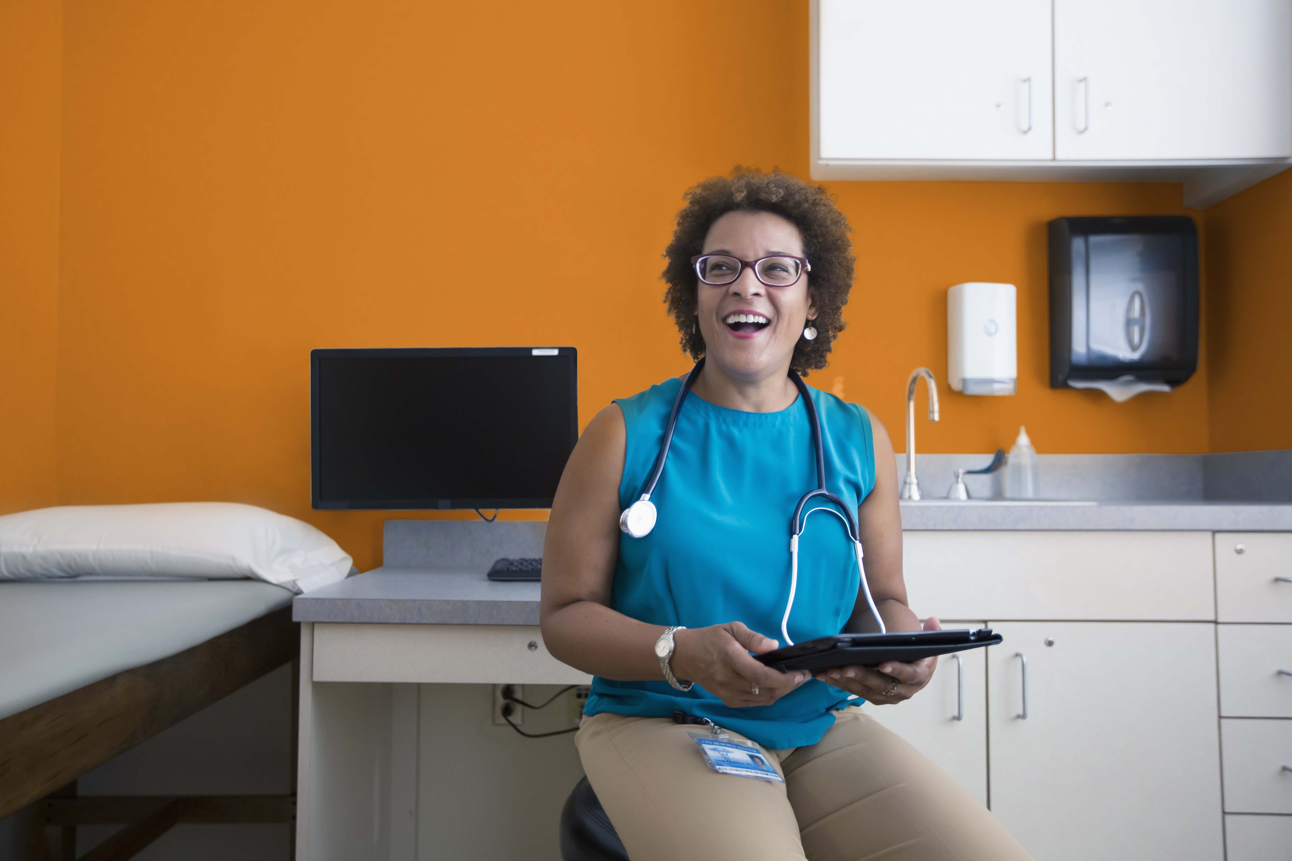 Female healthcare provider smiling and holding a tablet