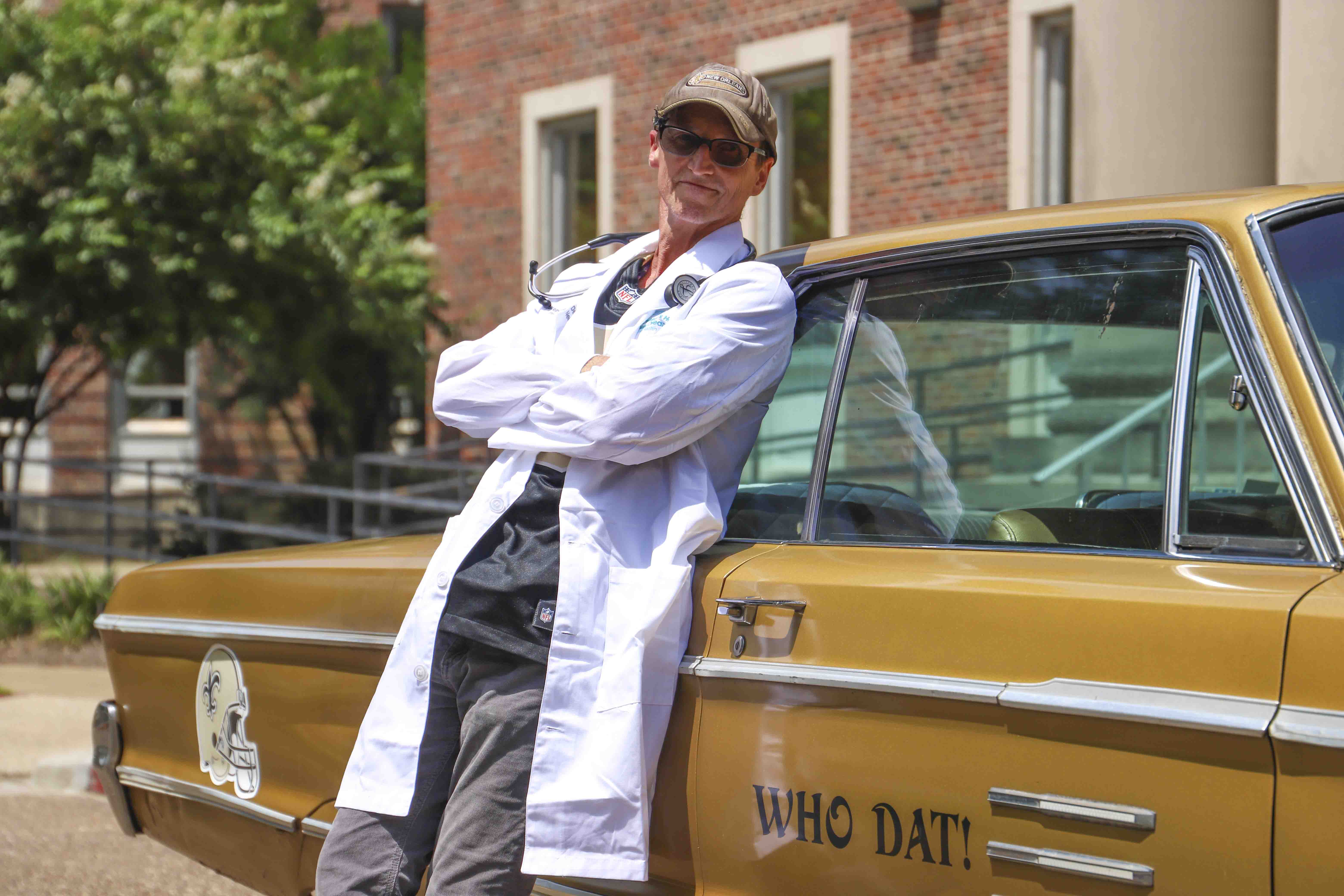 "Man in labcoat leaning against gold car that says ""Who Dat"""