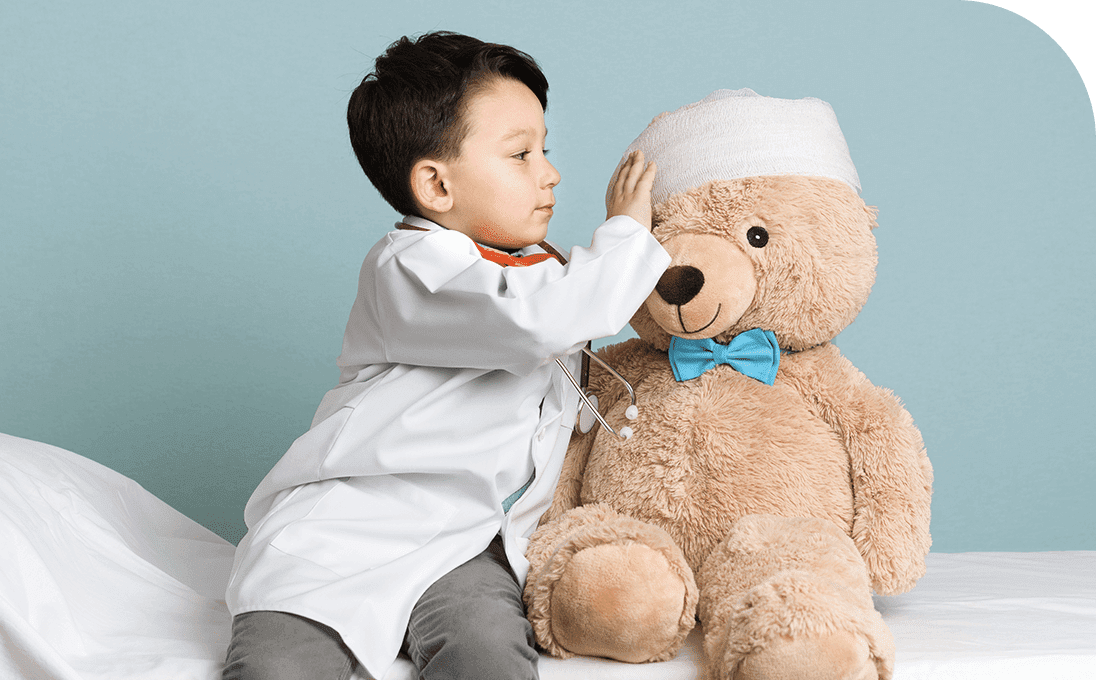 Little boy in doctor's coat playing doctor with a stuffed teddy bear